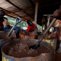 A young artisanal miner washes crushed rock containing gold in metal drums at the unlicensed mining site of Nsuaem Top in Ghana in November. | REUTERS
