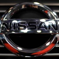 Nissan's logo is seen on a car during the Prague auto show on Saturday. | REUTERS