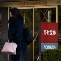 Pedestrians walk past a branch of Nomura Securities Co., a unit of Nomura Holdings Inc., in Kawasaki. | BLOOMBERG