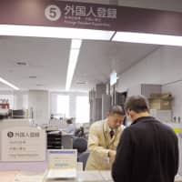A foreign resident registers at a ward office in Osaka. | KYODO