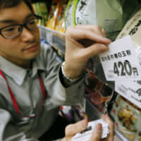 A supermarket worker replaces a price tag before Japan raised the consumption tax to 8 percent from 5 percent in 2014. | KYODO