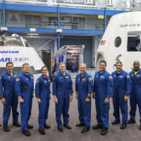 Mockups of Boeing's CST-100 Starliner and SpaceX's Crew Dragon capsules with crew members (from left) Sunita Williams, Josh Cassada, Eric Boe, Nicole Mann, Christopher Ferguson, Douglas Hurley, Robert Behnken, Michael Hopkins and Victor Glover are seen last year at the Johnson Space Center in Texas. | NASA / VIA AP