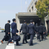 Transport ministry officials enter the headquarters of Suzuki Motor Corp. on Friday as part of an investigation into improper quality inspections related to the automaker's recall of more than 2 million cars in Japan. | KYODO