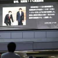 People walk past a large TV screen at JR Osaka Station in October 2018, showing news of Prime Minister Shinzo Abe's announcement that consumption tax would be raised as planned. | KYODO