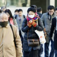 People commute to work in the Marunouchi district of central Tokyo. | KYODO