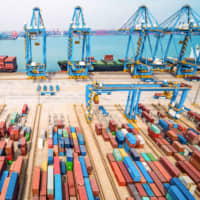 Cranes load cargo on freighters at a port in Qingdao in China's eastern Shandong province. The U.S. has reportedly watered down its demand for China to end trade subsidies. | AFP-JIJI