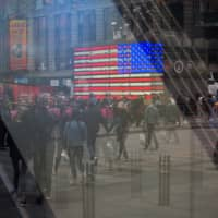 Pedestrians are reflected in a window of the Nasdaq MarketSite in the Times Square neighborhood of New York on Monday. U.S. stocks pared losses as investors awaited signs of progress in the trade war with China ahead of the latest corporate earnings season. | BLOOMBERG