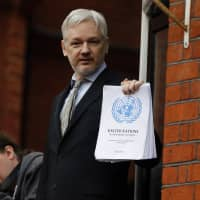WikiLeaks founder Julian Assange stands on the balcony of the Ecuadorean Embassy to address waiting supporters and media in London on Feb. 5, 2016. Police in London arrested Assange on Thursday for failing to surrender to the court in 2012, shortly after the South American nation revoked his asylum. | AP