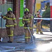 Firemen wash away bloodstains on the sidewalk after a security guard was shot dead during a drive-by shooting outside a popular Melbourne nightclub early Sunday. | AFP-JIJI
