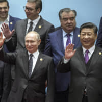 Chile's President Sebastian Pinera (front left), Russian President Vladimir Putin and Chinese President Xi Jinping wave while posing during the Belt and Road Forum in Beijing on Saturday. | AP