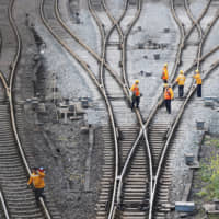 Workers inspect railway tracks that serve as a part of the 'Belt and Road' freight rail route linking Chongqing, China, to Duisburg, Germany, at the Dazhou railway station in Sichuan province, China, on March 14. | REUTERS