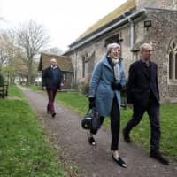 Britain's Prime Minister Theresa May and her husband, Philip, leave church near High Wycombe, England, on Sunday. | REUTERS
