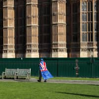 A lone activist against Brexit walks outside the Houses of Parliament in London on Thursday. | BLOOMBERG