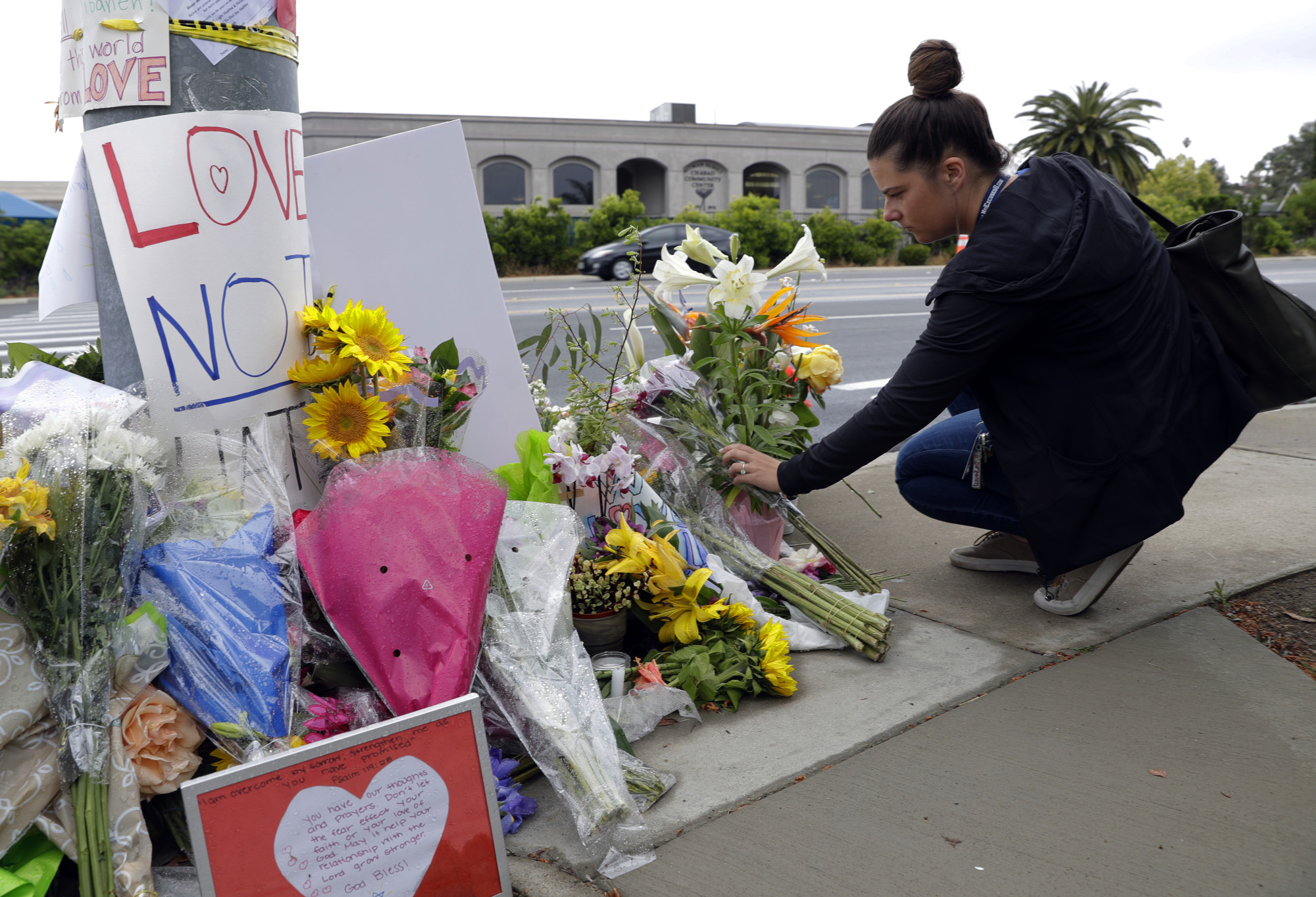 A woman leaves flowers on a growing memorial across the street from the Chabad of Poway synagogue in Poway, California, on Monday. A gunman opened fire on Saturday as dozens of people were worshipping exactly six months after a mass shooting in a Pittsburgh synagogue. | AP