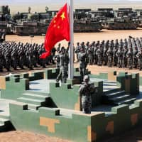 Soldiers of China's People's Liberation Army raise a Chinese flag during a military parade to commemorate the 90th anniversary of the foundation of the army at a training base in China's Inner Mongolia Autonomous Region in 2017. | REUTERS