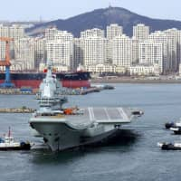 China's first domestically developed aircraft carrier with aircraft on its deck departs port for its fourth sea trial in Dalian, Liaoning province, last December. | REUTERS