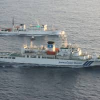 A Chinese patrol ship (top) sails side by side with a Japan Coast Guard patrol vessel in 2011 near disputed islands in the East China Sea, known as the Senkakus in Japan and Diaoyu in China. | REUTERS
