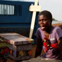 A woman cries during the funeral of a child, suspected of dying from Ebola, next to the coffin in Beni, North Kivu Province of Democratic Republic of Congo, last December. | REUTERS