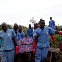 Red Cross workers carry the coffin of an Ebola victim to be buried in the eastern town of Butembo in the Democratic Republic of Congo March 28. | REUTERS