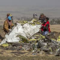 Rescuers work at the scene of an Ethiopian Airlines jetliner crash near Bishoftu, or Debre Zeit, south of Addis Ababa March 11. Pilots of the Ethiopian Airlines flight encountered problems with their new Boeing jetliner from nearly the moment they roared down the runway and took off. Ethiopian authorities issued a preliminary report Thursday on the March 10 crash. | AP