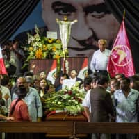 Supporters of the late Peruvian ex-President Alan Garcia pay respects during his wake at the American Popular Revolutionary Alliance (APRA) party headquarters in Lima Thursday. | AFP-JIJI