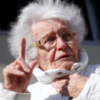 Lisel Heise, a 100-year-old former sports instructor, answers a reporter's question in front of the town hall in Kirchheimbolanden, Germany, on Thursday. The centenarian decided to engage in local politics and will run in the town's upcoming local elections at the end of May. | REUTERS