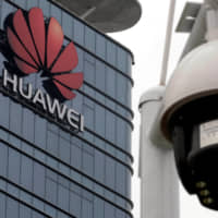A surveillance camera is seen in front of the Huawei logo outside its factory campus in Dongguan, in China's Guangdong province,  on March 25. | REUTERS