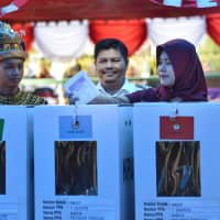 A woman casts her vote Wednesday in Trumon, Southern Aceh province, as Indonesia kicks off one of the world's biggest one-day elections. | AFP-JIJI