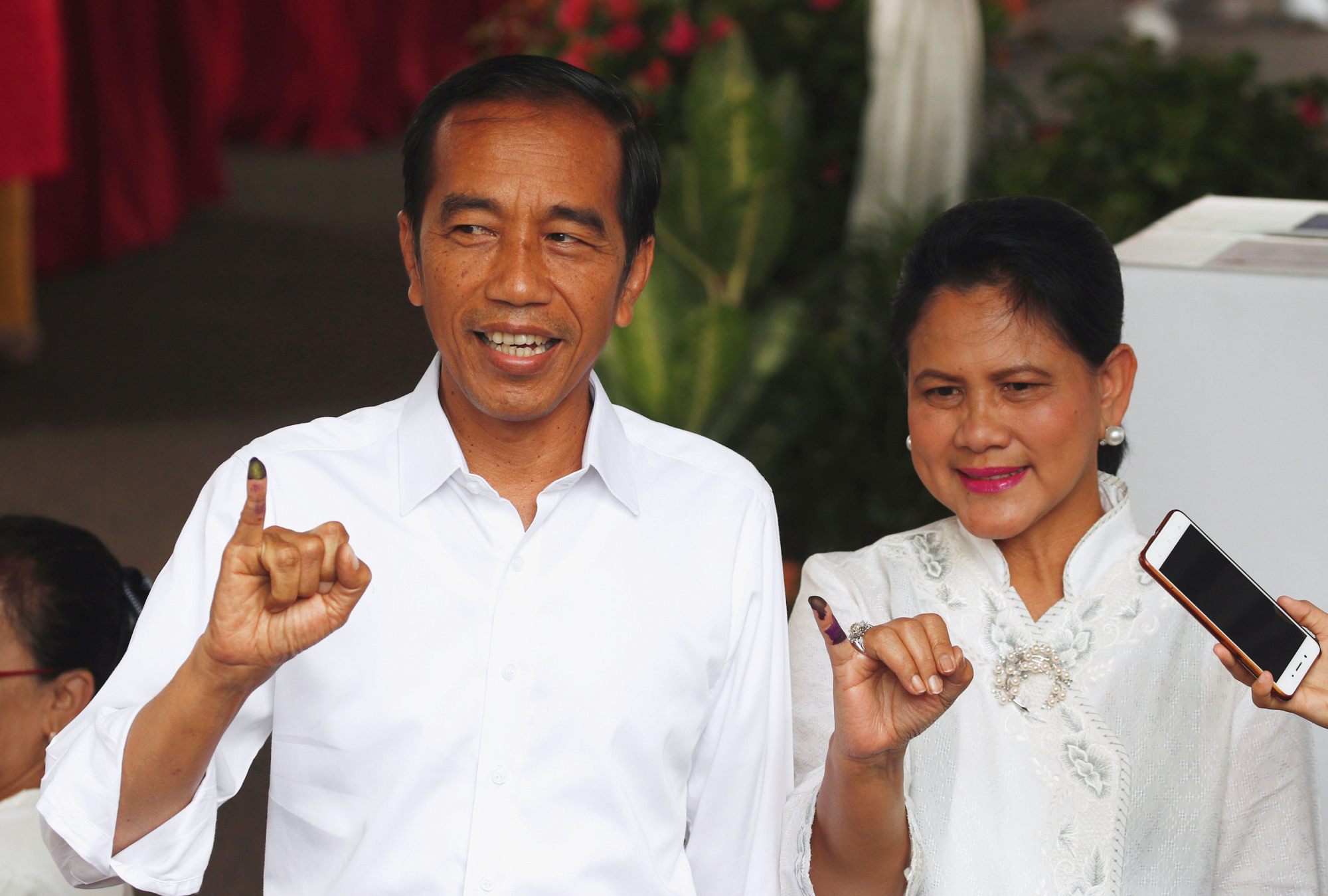 Indonesian President Joko Widodo and first lady Iriana Joko Widodo show their ink-stained fingers after casting their ballots during elections in Jakarta, Indonesia, on Wednesday. | REUTERS
