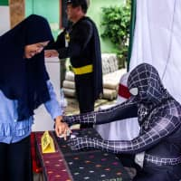 Indonesian election workers dressed in superhero costumes register voters at a polling station in Surabaya on Wednesday. | AFP-JIJI