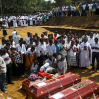 People react during a mass burial of victims two days after a string of suicide bomb attacks on churches and luxury hotels across the island on Easter Sunday, at a cemetery near St. Sebastian Church in Negombo, Sri Lanka, Tuesday. | REUTERS