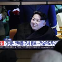 People watch a TV news program reporting about North Korea's test-fire of a 'new-type tactical guided weapon,' with a file footage of North Korean leader Kim Jong Un, at the main railway station in Seoul on Thursday. | AP