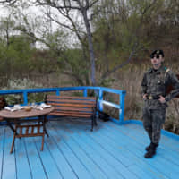 A South Korean soldier stands on the blue bridge ahead of a ceremony to mark the first year anniversary of the Panmunjom Declaration on the southern side of Panmunjom in the Demilitarized Zone on Saturday. The agreement was adopted by South Korean President Moon Jae-in and North Korean leader Kim Jong Un on April 27, 2018. | REUTERS