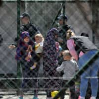 Police officers guard women and children who are relatives of Kosovo Jihadis who returned from Syria, at the foreigner detention center in Pristina Saturday. | REUTERS
