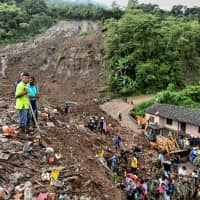 People search for victims after a landslide in Rosas, Valle del Cauca department, in southwestern Colombia, on Sunday. At least 14 people were killed and five others injured by a mudslide that buried eight houses early Sunday in southwestern Colombia, authorities said. | AFP-JIJI