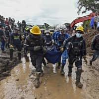 Rescue workers carry a corpse after a landslide in Rosas, Valle del Cauca department, in southwestern Colombia, on Sunday. At least 14 people were killed and five others injured by a mudslide that buried eight houses early Sunday. | AFP-JIJI