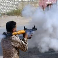 A fighter loyal to Libya's internationally recognized government fires a rocket-propelled grenade during clashes with forces loyal to strongman Khalifa Hifter south of Tripoli's suburb of Ain Zara on Saturday. | AFP-JIJI