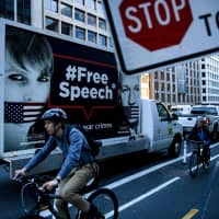 Cyclists pass a truck with a protest sign on it reading '#FreeSpeech' with pictures of Chelsea Manning (left) and WikiLeaks founder Julian Assange, in Washington on April 16. | AFP-JIJI