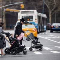 A Jewish man and two woman push strollers as they cross a street in a Jewish quarter in Williamsburg Brooklyn in New York City April 9. The origins of the measles outbreak in the United States are not a mystery. Persons infected with the virus brought it to the United States from Israel and Ukraine and passed it on to members of their tight-knit communities, many of whom had not been vaccinated. | AFP-JIJI