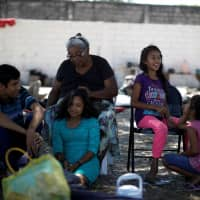A family from Honduras sits near their tents at an improvised shelter while waiting for a humanitarian visa to cross the country on their way to the United States, in Mapastepec, Chiapas state, Mexico, Sunday. | REUTERS