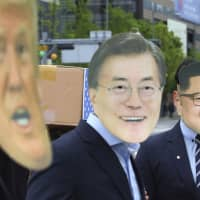 Protesters wear masks of U.S. President Donald Trump, South Korean President Moon Jae-in and North Korean leader Kim Jong Un during a rally demanding peace on the Korean Peninsula, near the U.S. Embassy in Seoul on Friday. | AP