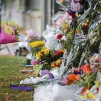 A little girl carries flowers to a memorial wall on March 17 following the mosque shootings in Christchurch, New Zealand, that left 50 dead and 39 wounded two days earlier. New Zealand's parliament on Wednesday passed sweeping gun laws that outlaw military-style weapons. | AP