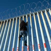 A Central American migrant climbs the U.S.-Mexico border fence in Playas de Tijuana, Baja California State, Mexico, in December. | AFP-JIJI