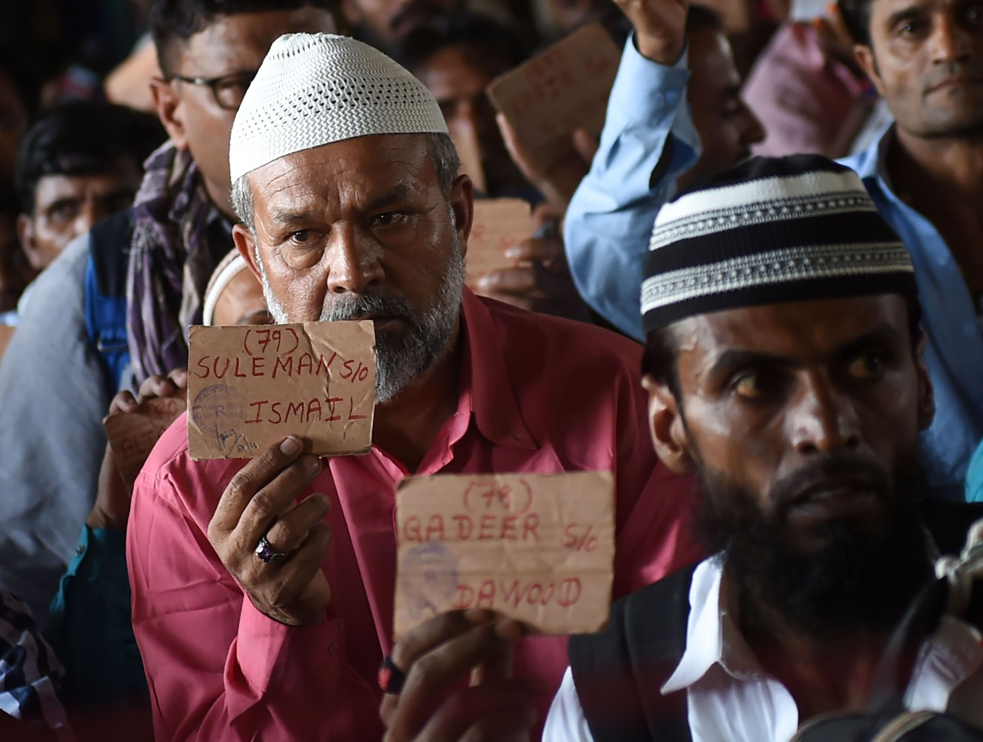 Indian fishermen show their travel cards as they sit at a railway station in Karachi, Pakistan, Sunday  after they were released from the Malir Jail. Pakistan released 100 Indian fishermen held for trespassing into its territorial waters, officials said. | AFP-JIJI