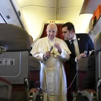 Pope Francis, flanked by interim director of Holy See Press Office Alessandro Gisotti, speaks to reporters on board the flight back to Rome from a two-day trip to Morocco Sunday. Francis sought Sunday to encourage greater fraternity between Christians and Muslims in Morocco, telling his flock that showing the country's Muslim majority they are part of the same human family will help stamp out extremism. | ALBERTO PIZZOLI / POOL PHOTO / VIA AP