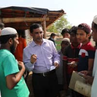 Mohib Ullah, a leader of  the Arakan Rohingya Society for Peace and Human Rights, speaks to other Rohingya people who face difficulty collecting relief supplies in Kutupalong camp in Cox's Bazar, Bangladesh, on April 7. | REUTERS