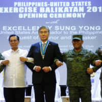 Philippine Armed Forces Southern Luzon Command Chief Lt. Gen. Gilbert Gapay (from left), Undersecretary of National Defense Cardozo Luna, U.S. Ambassador to the Philippines Sung Kim, Armed Forces of the Philippines Chief Gen. Benjamin Madrigal Jr. and Brig. Gen. Christopher McPhillips link arms during the opening ceremony of the joint U.S.-Philippine military exercise Balikatan 2019 on Monday at Camp Aguinaldo, northeast of Manila. | AP