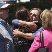 Members of the Congregation Chabad synagogue in the town of Poway, California, hug as they gather near the Altman Family Chabad Community Center on Saturday. A shooting at the synagogue outside San Diego, where worshippers were celebrating the last day of Passover, left one dead and three injured. | AP