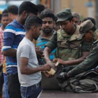 Sri Lankan army personnel search people and their bags at a check point in Kattankudy, near Batticaloa, on Sunday. | REUTERS
