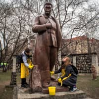 Volunteers clean a monument representing Soviet leader Josef Stalin during a spring community work day at the Muzeon Park of Arts in Moscow on Saturday. | AFP-JIJI